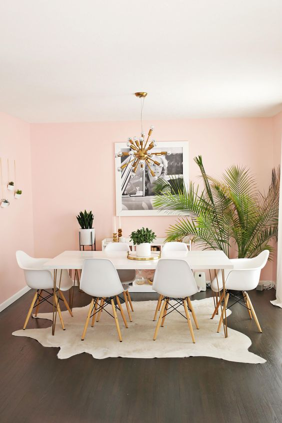 a tropical glam dining room with light pink walls, a hairpin leg dining table, white chairs, a sunburst chandelier and some tropical plants