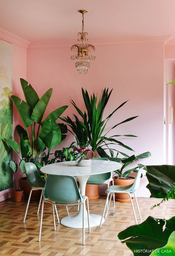 a tropical glam dining room with pink walls, a round table, green chairs, a whimsical chandelier and lots of potted plants