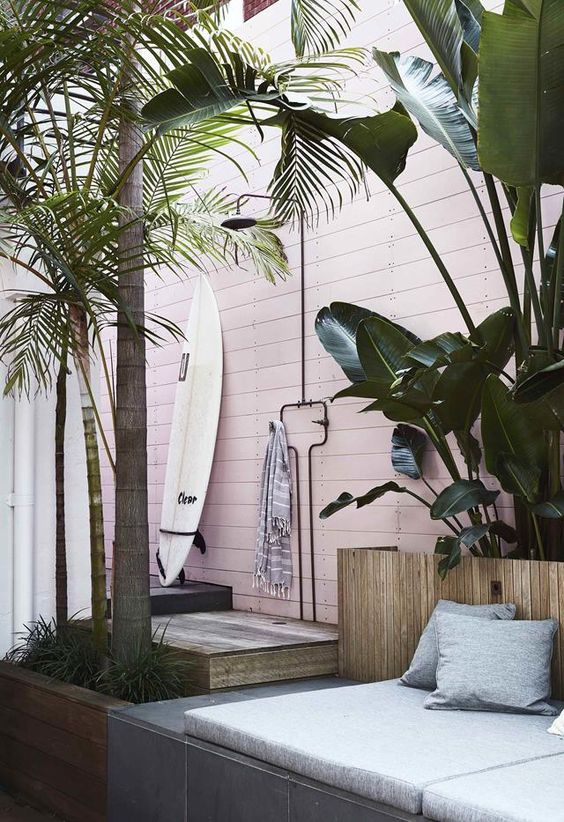 a tropical outdoor shower with a pink planed wall, a wooden deck, a surf board and a striped towel and tropical plants around