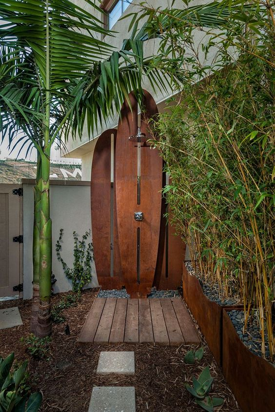 a tropical shower with a wall formed of wooden surf boards, a wooden deck and lots of plants growing around