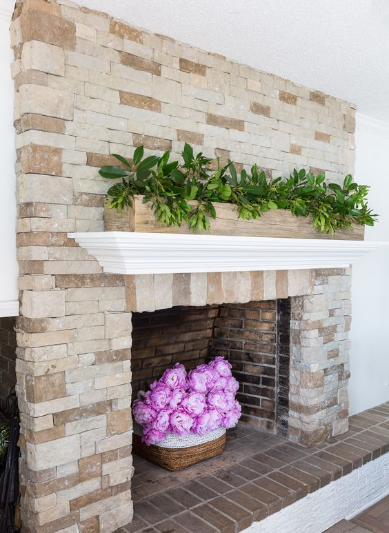 a very easy and chic summer mantel and fireplace decor with a long planter with greenery and hot pink peonies in a basket is wow