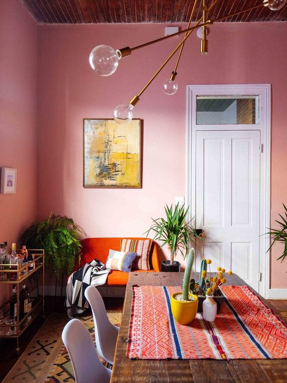 a vibrant dining room with pink walls, an orange loveseat, a dinind table with a colorful runner, some plants and a bar cart
