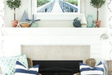 a vintage coastal mantel with potted greenery, mini boats, starfish, a photo in a whitewashed wooden frame and a rope ball