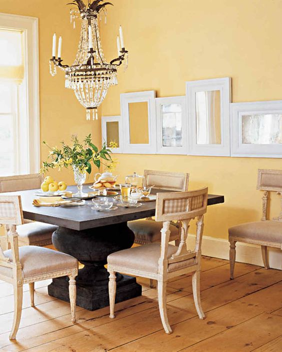 a vintage dining room with yellow walls, a vintage dark stained table, vintage neutral chairs, a crystal chandelier and a ledge with frames
