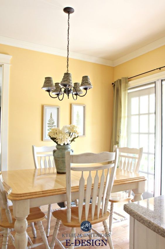 a vintage dining space with yellow walls, a vintage dining set, a vintage chandelier and a large window with yellow plaid curtains