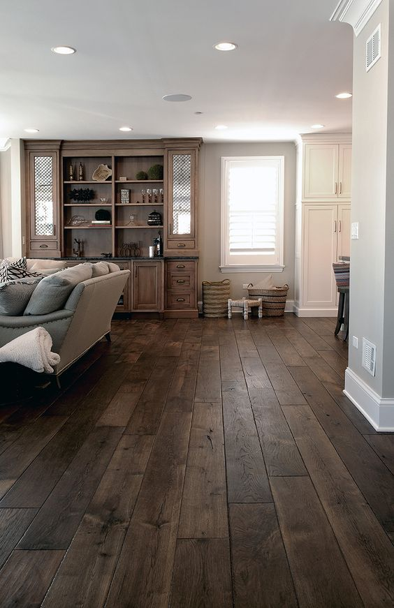 a vintage farmhouse living room with dark stained hardwood floors, vintage funriture and a large storage unit is lovely