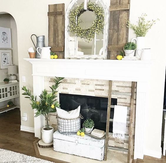 a vintage summer mantel with lemons, greenery in vases and pits, a mirror, a yellow floral wreath and jugs