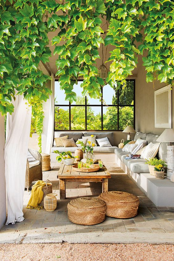 a welcoming Mediterranean terrace with a built-in corner sofa,  a low wooden table, baskets, lanterns and greenery and blooms