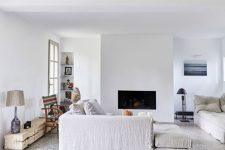 a welcoming living room in white, with a pretty terrazzo floor, a built-in fireplace and ecletic furniture pieces