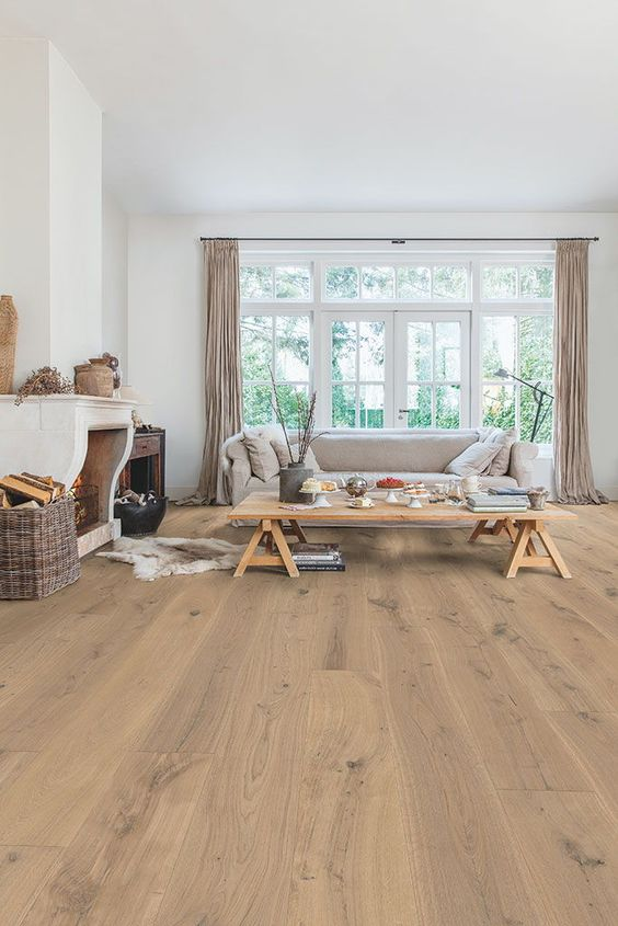 a welcoming living room with much negative space, lovely hardwood flooring, cool rustic furniture and neutral textiles