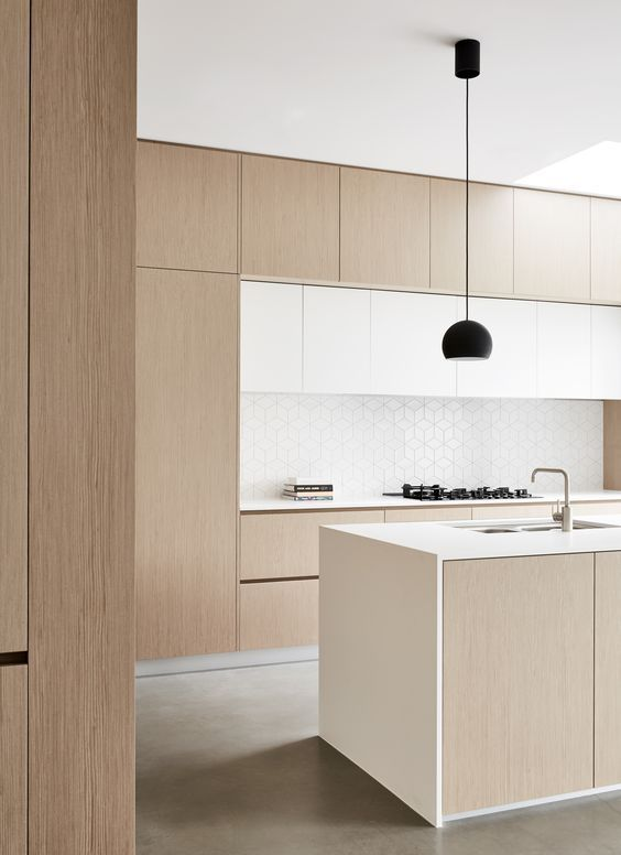 a welcoming minimalist kitchen with white and light stained sleek cabinetry, a geometric tile backsplash and black pendant lamps