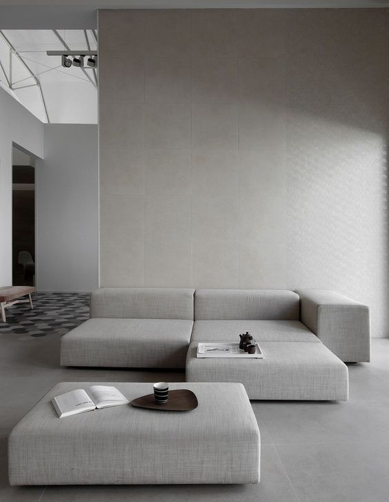 a welcoming minimalist living room done in light greys, with a sectional and a square ottoman is a chic idea