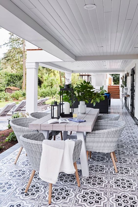 a welcoming outdoor dining space with a mosaic tile floor, a table with a thick tabletop, wicker chairs and a potted tree plus candle lanterns