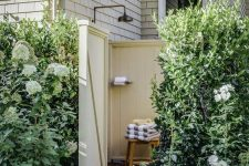 a welcoming outdoor shower with yellow planked walls and a stained wooden mat on the ground, a wooden stool and printed and bright towels