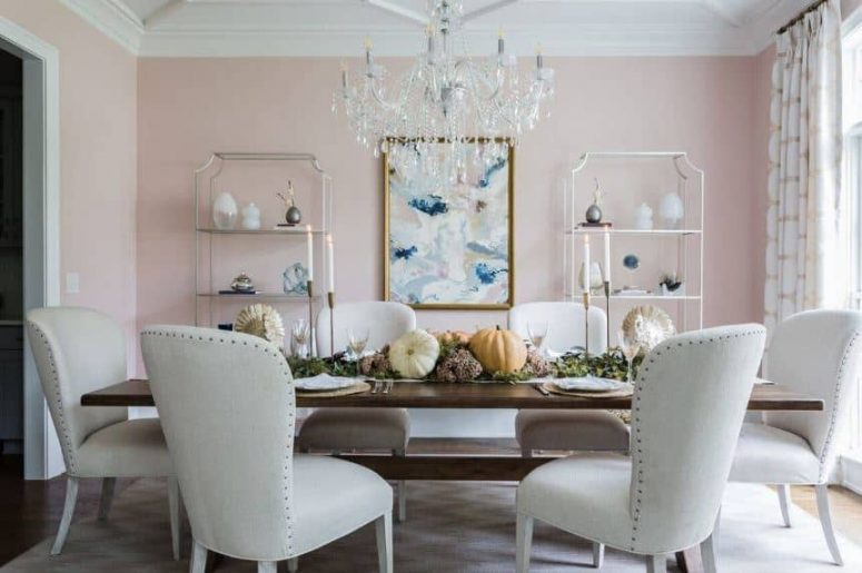 a welcoming refined dining room with blush walls, matching shelving units, a crystal chandelier, a wooden table and white upholstered chairs