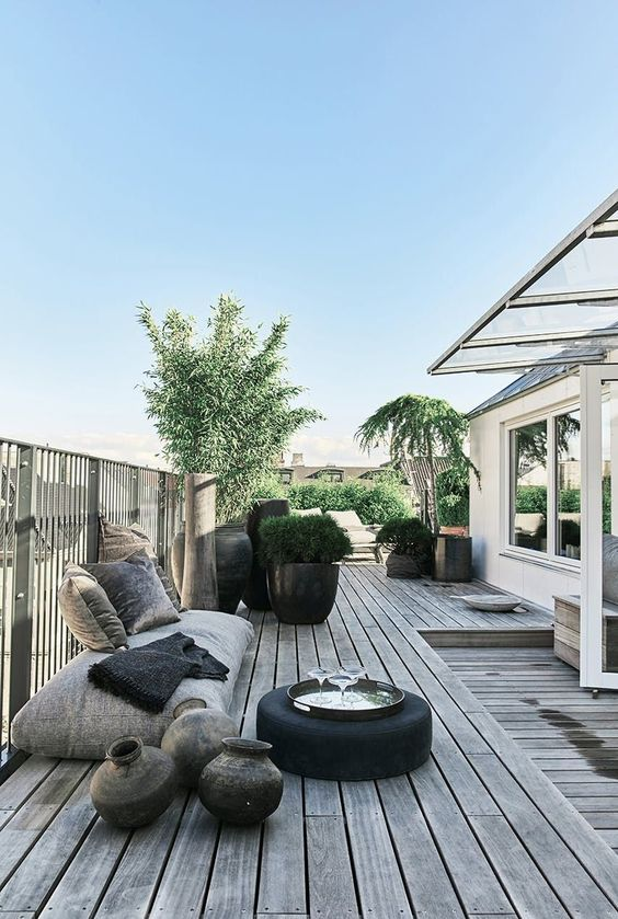 a welcoming rooftop terrace with a wooden deck, modern furniture, cushions and pillows, potted plants and trees