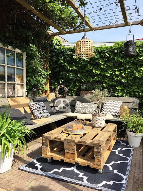 a welcoming summer terrace with a corner bench and printed pillows, a pallet coffee table, a pendant lamp and lights and potted greenery