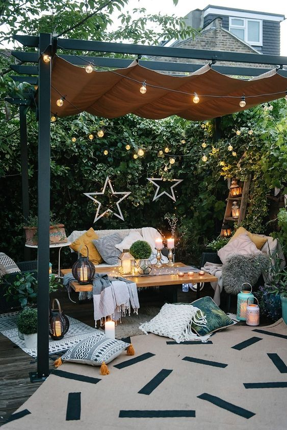 a welcoming summer terrace with a sofa, some chairs, a coffee table, printed rugs, pillows, candles, candle lanterns and star decor