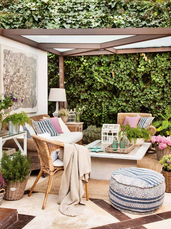 a welcoming summer terrace with woven furniture, a small coffee table, layered rugs, printed pillows and blankets