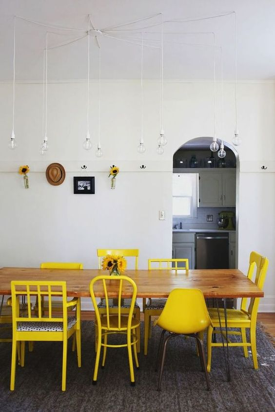 a whimsical dining room with a long hairpin leg table, mismatching yellow chairs, pendant lamps and decor on the wall