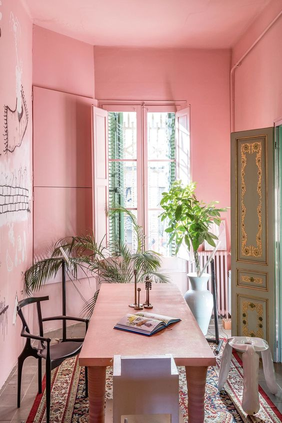 a whimsical pink eat-kitchen with a big dining zone, a pink table, chairs and even shutters on the window looks pop-art and very tropical