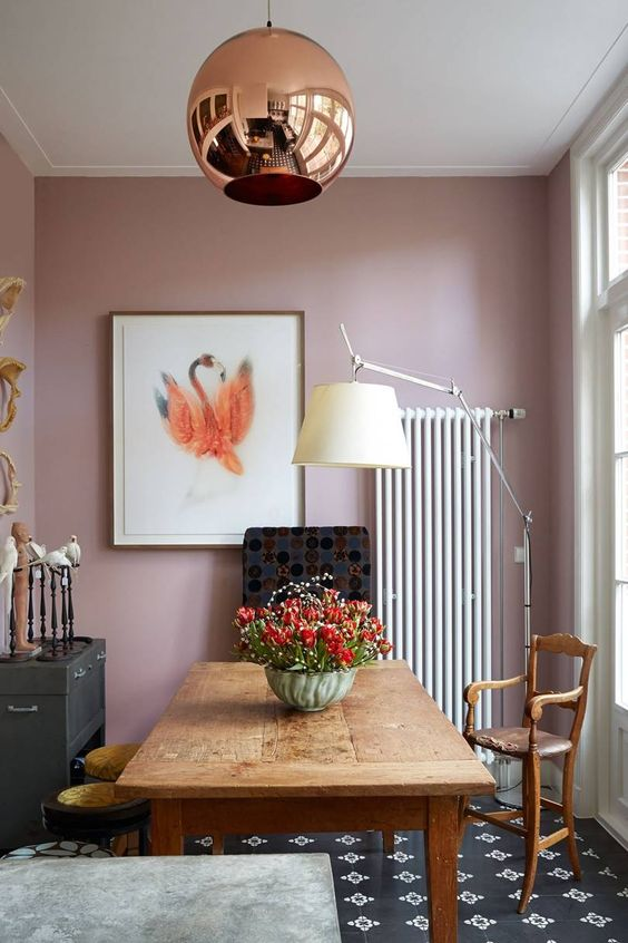 a whimsy dining room with pink walls, a vintage wooden dining table, chairs and stools, a copper sphere pendant lamp and some art
