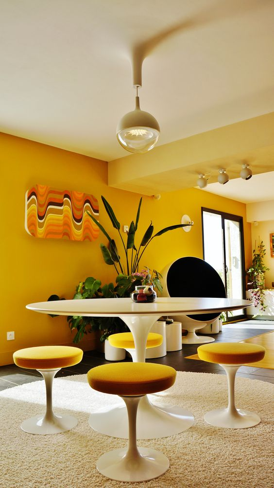 a whimsy modern yellow dining space with yellow wlals, a round table and yellow round stools, a catchy artwork and a sphere lamp