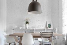 a white Scandinavian dining space with white brick walls and white beams on the ceiling, a lovely dining set and neutral hardwood floors