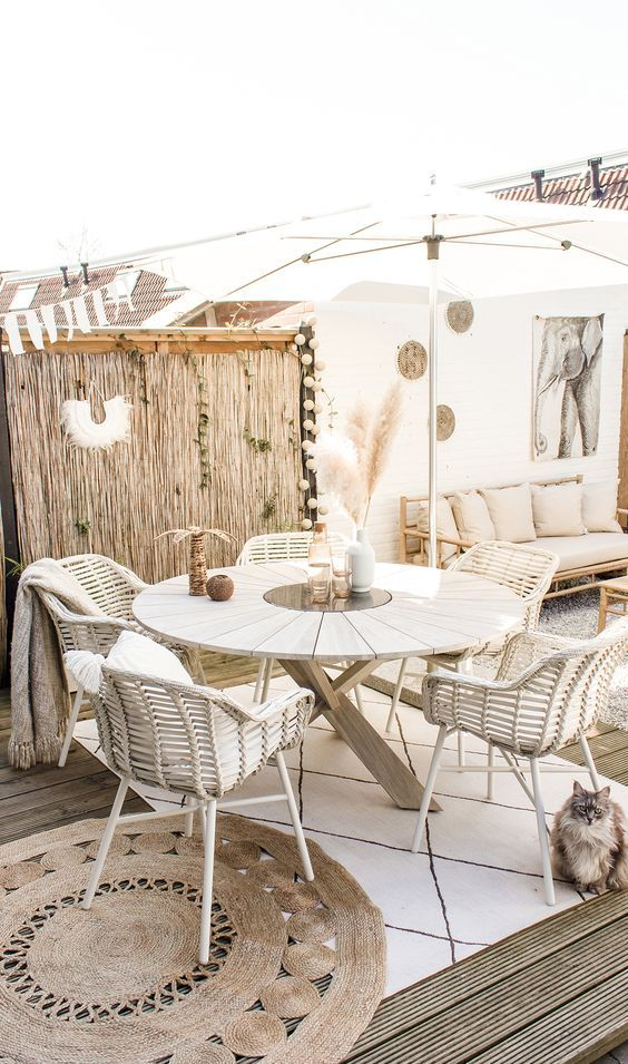 a white boho outdoor dining space with a round table, white wicker chairs, pampas grass, an umbrella and some jute rugs