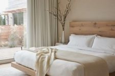a zen minimalist bedroom with dove grey walls, ligth grene curtains, a stained floating bed and neutral bedding is welcoming