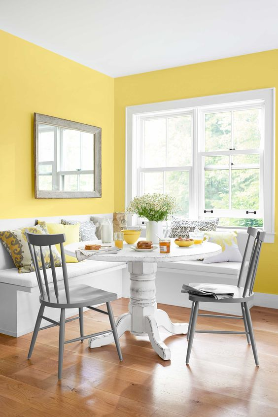 an airy country dining space with sunny yellow walls, a built-in bench and a white heavy table, grey chairs and bright printed pillows