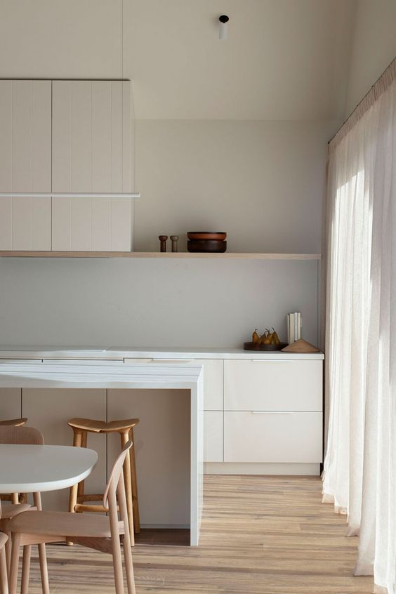 an airy minimalist kitchen in white, with planked cabinetry, an open shelf, neutral curtains and a lovely dining set