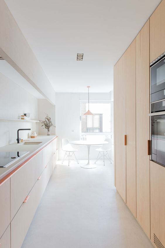 an airy minimalist kitchen with light stained cabinetry, white countertops and a backsplash, black fixtures and much natural light
