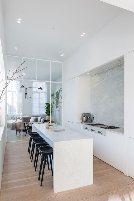 an airy white minimalist kitchen with sleek cabinetry, a kitchen island with a waterfall countertop and black stools
