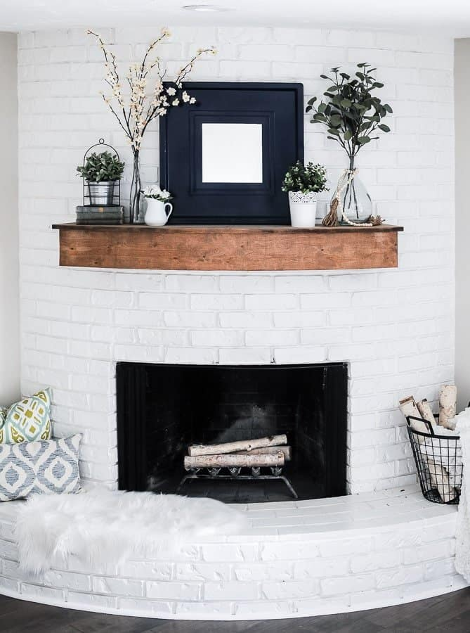 an easy farmhouse summer mantel with greenery arrangements, potted plants, a mirror in a wide frame and some books