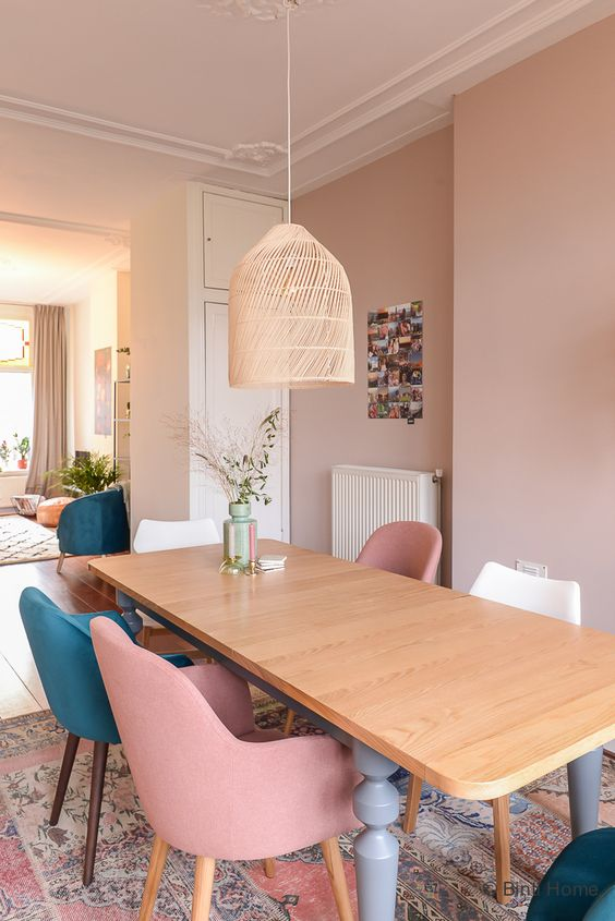 an eclectic dining room with dusty pink walls, a wooden dining table, pink, teal and white chairs and a woven pendant lam[