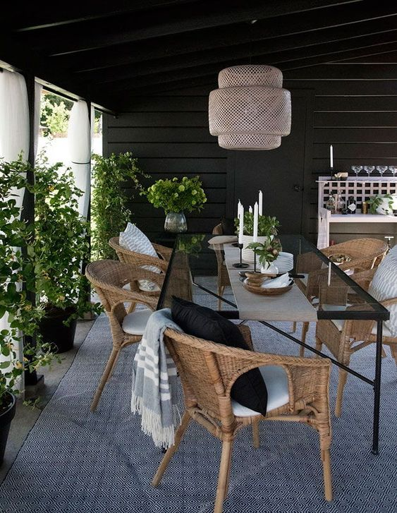 an elegant and cool outdoor-indoor dining room with a glass table and woven chairs, a woven pendant lamp and potted greenery