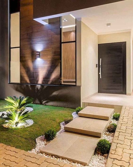 an elegant and modern front yard with stone tiles, neutral pebbles, greenery, grass and tropical plants with additional lights
