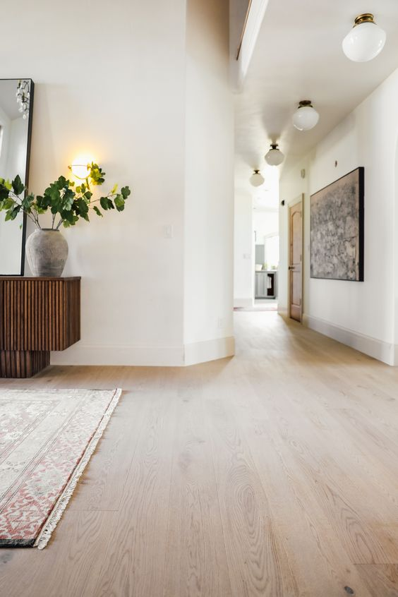 an elegant and refined space with white walls, light stained hardwood flooring, chic and stylish furniture and lovely lamps