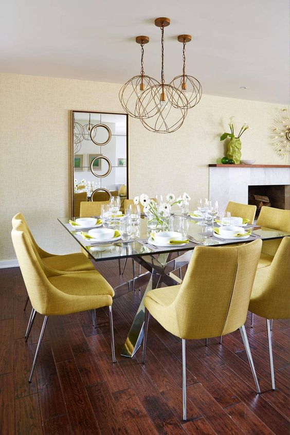an elegant dining room with pale yellow walls, a glass table, yellow chairs, a mirror, a cluster of pendant lamps