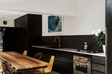 an elegant kitchen with a black and white terrazzo floor, dark stained cabinets, a stained table and woven chairs is lovely
