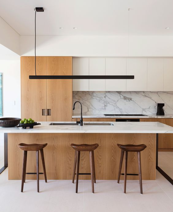 an elegant minimalist kitchen with white and light stained cabinetry, a large kitchen island, a marble backsplash and wooden stools