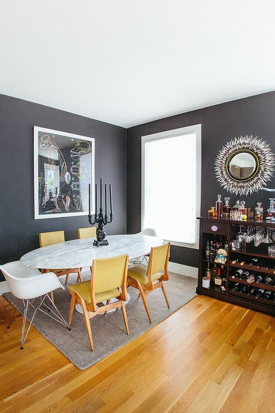 an elegant moody dining space with black walls, an oval table and yellow chairs that echo with a light stained floor
