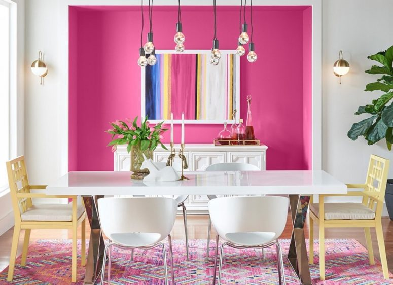 an eye-catchy dining room with a hot pink niche with a bar, a long dining table and mismatching chairs plus bulbs over the space