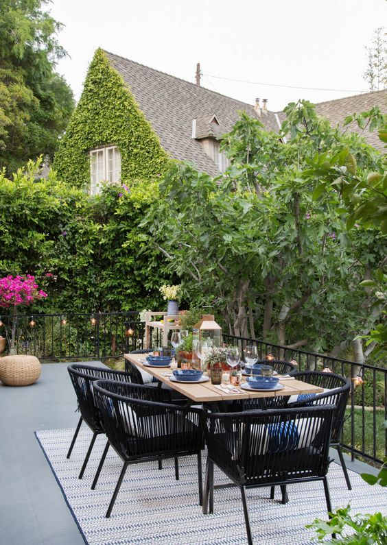 an inviting outdoor dining space with a lightweight table, black wicker chairs, potted greenery and blooms and candle lanterns