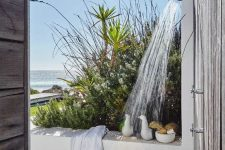 an outdoor shower with a sea view, a wooden deck and a bamboo floor, some shower stuff and towels