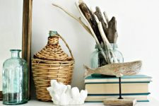 beautiful coastal mantel decor with a mirror in a wooden frame, aqua bottles, blue books, driftwood in a jar, a wooden whale and corals