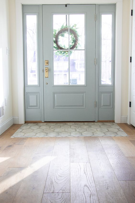 engineered hardwood flooring makes this rustic entryway very chic and very stylish, and a bit of tile helps to keep the hardwood floor in order