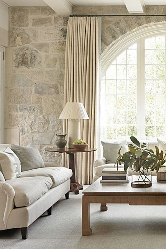 a French farmhouse living room in neutrals with a large arched French window, neutral furniture, a low coffee table and greenery