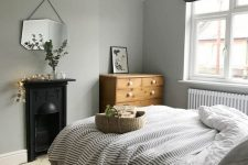 a Nordic bedroom with grey walls, a vintage built-in hearth, a bed with neutral and printed bedding, a stained dresser and a mirror